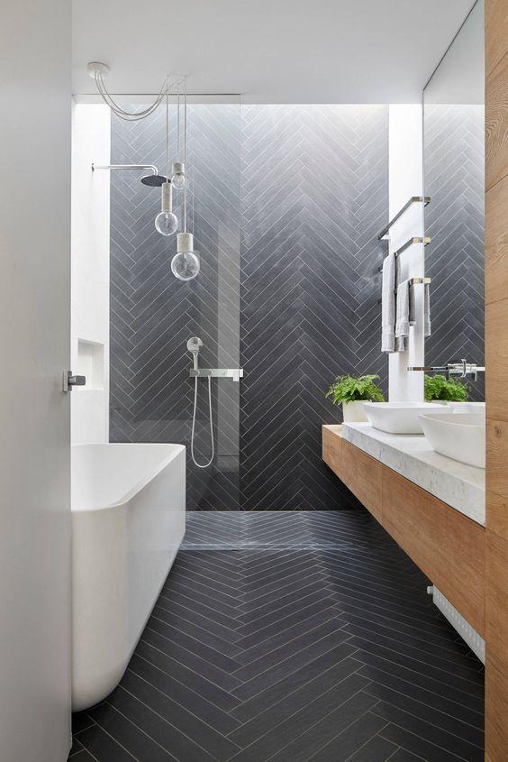 un bagno contemporaneo rivestito con piastrelle grigio grafite lunghe e sottili in un motivo a chevron