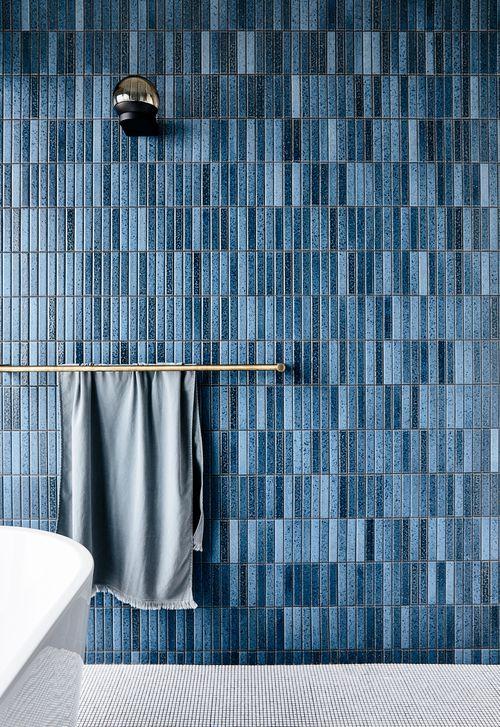 un elegante bagno contemporaneo con un pavimento grigio, un muro di piastrelle skinny blu navy e tocchi in ottone sembra chic