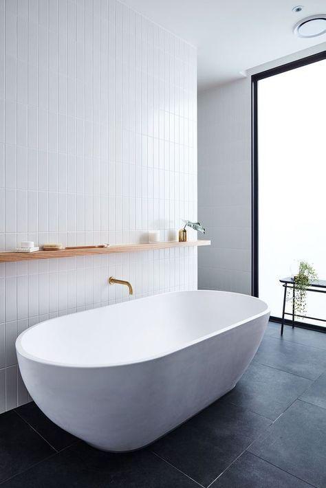 un bagno minimalista chic con piastrelle bianche sottili sul muro e una vasca ovale bianca più piastrelle nere sul pavimento