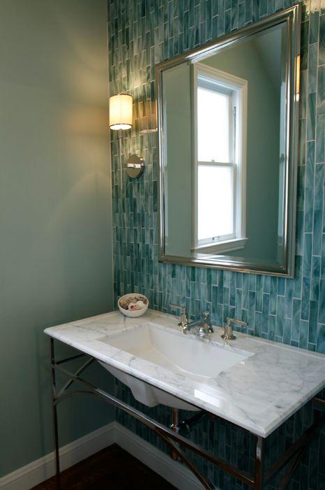 un elegante bagno di ispirazione vintage con pareti verde menta e un muro di piastrelle turchesi magro più un lavandino rivestito in marmo