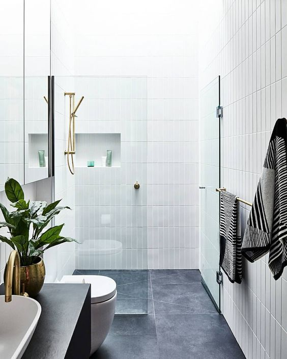 un elegante bagno contemporaneo con piastrelle grigie sul pavimento e piastrelle bianche sottili sulle pareti più nicchie