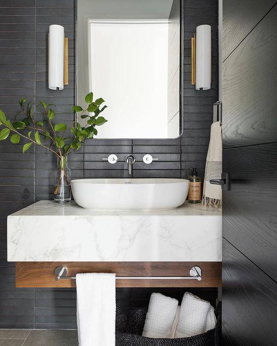 un bagno moderno con piastrelle skinny nere opache sul muro più una vanità galleggiante in legno e marmo