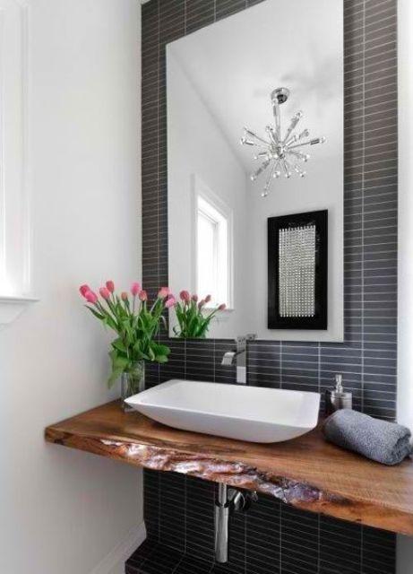 un bagno moderno con un muro di piastrelle skinny blu scuro, una vanità galleggiante dal bordo vivo e un lavandino geometrico