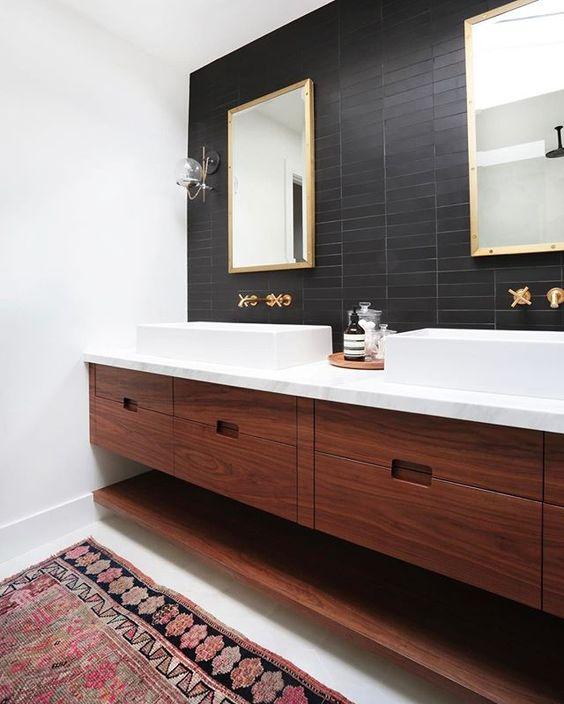 un bagno moderno della metà del secolo con piastrelle nere sottili sul muro accento che contrastano i lavandini bianchi