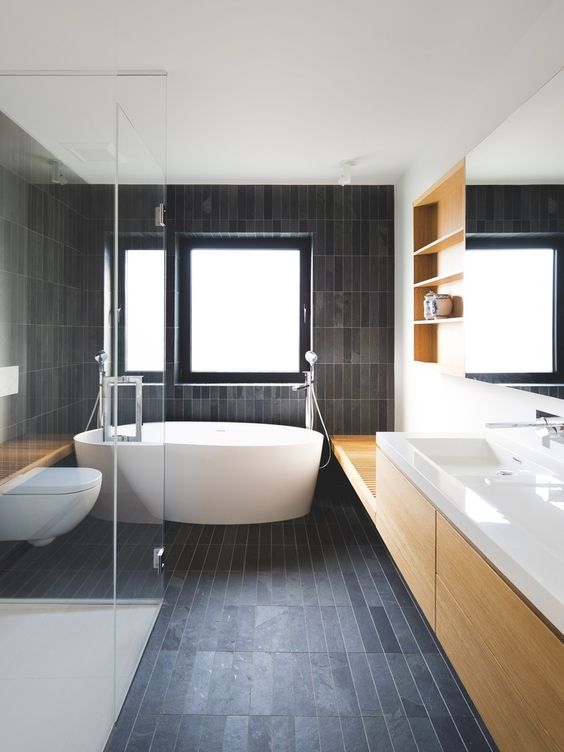 un bagno contemporaneo, tutto rivestito con piastrelle skinny scure opache e rinfrescato con legno di colore chiaro e pezzi bianchi
