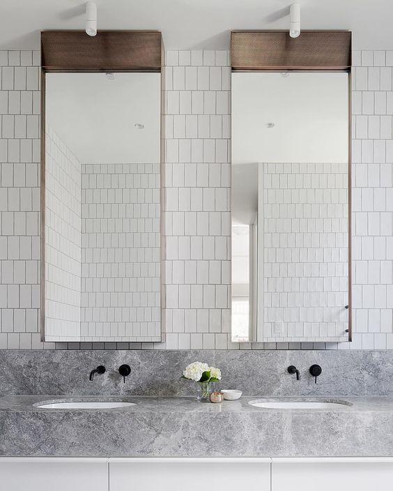 uno spazio minimalista con lavandino con piastrelle bianche sul muro, specchi accattivanti, un lavabo in marmo grigio