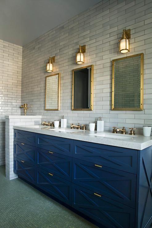 un bagno in stile art déco con piastrelle in marmo sottili, un luminoso lavabo blu e tocchi di ottone qua e là