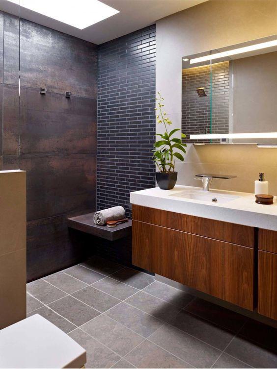 uno spazio doccia fatto con un muro di metallo invecchiato e un muro di accento di piastrelle skinny blu scuro più una panca galleggiante di metallo