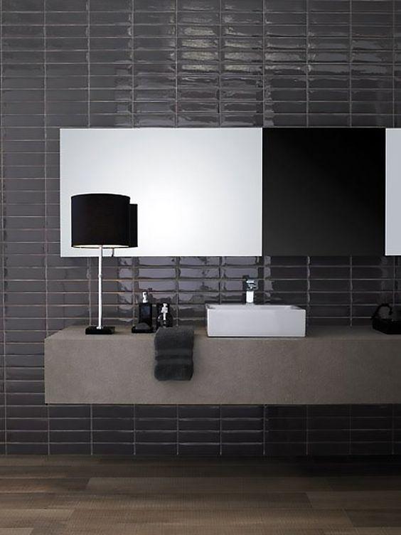 un bagno lunatico con piastrelle nere magre e lucide sul muro e una vanità fluttuante in cemento per un contrasto