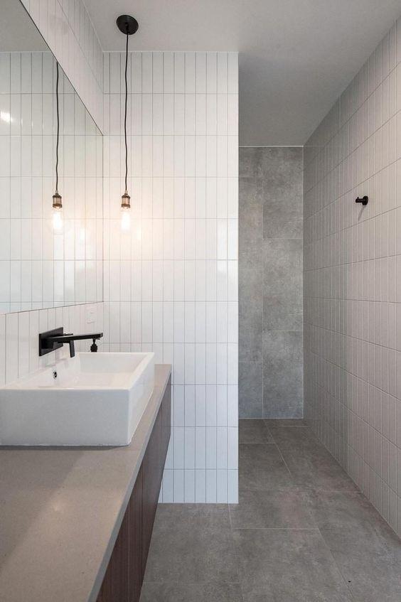 un bagno minimalista fatto con piastrelle grigie e bianche magre per un tocco accattivante