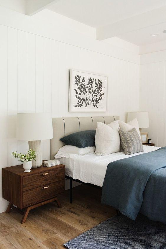 un'audace camera da letto moderna della metà del secolo con un letto in pelle grigia, comodini macchiati di scuro, tappeti e biancheria da letto blu scuro