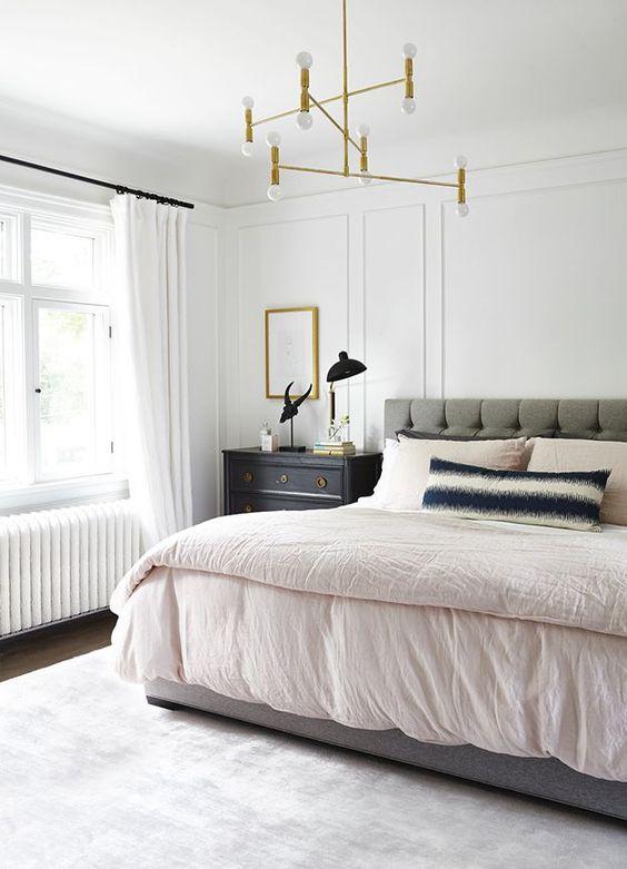 una rilassante camera da letto moderna della metà del secolo con un letto imbottito grigio, un lampadario dorato, comodini macchiati scuri e un tappeto neutro