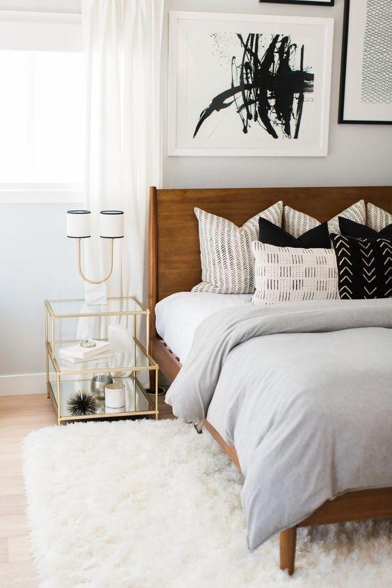 una luminosa camera da letto moderna della metà del secolo con un ricco letto colorato, un soffice tappeto bianco, un comodino con cornice dorata e un'opera d'arte astratta