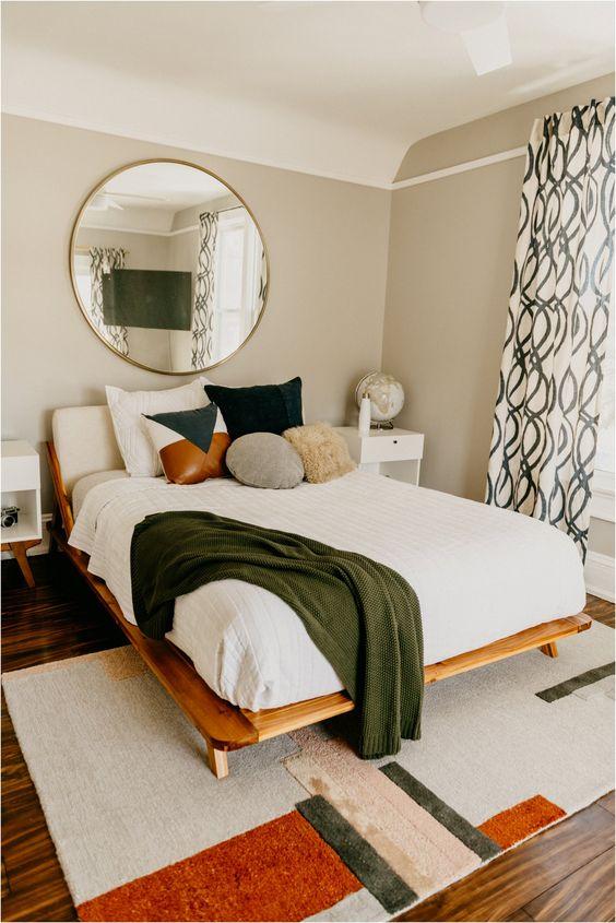 una camera da letto moderna della metà del secolo con un tappeto geometrico, un letto in legno, uno specchio rotondo, tende stampate e una varietà di cuscini