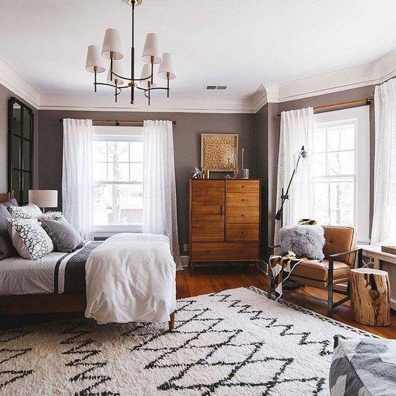 un'elegante camera da letto moderna della metà del secolo con un comò in legno ricco di tinte, una sedia in pelle, un tappeto stampato e un lampadario chic