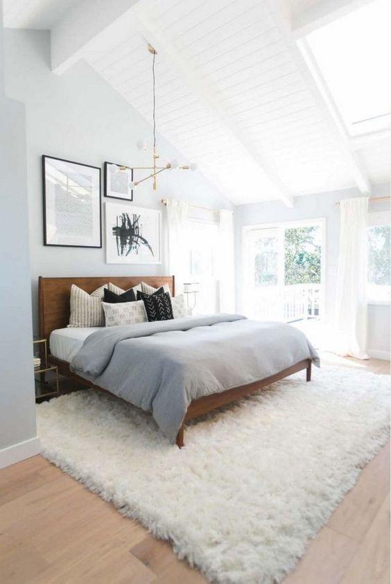 una camera da letto moderna della metà del secolo piena di luce con un letto in legno ricco di tinte, un soffice tappeto, un lampadario geometrico e una galleria a parete