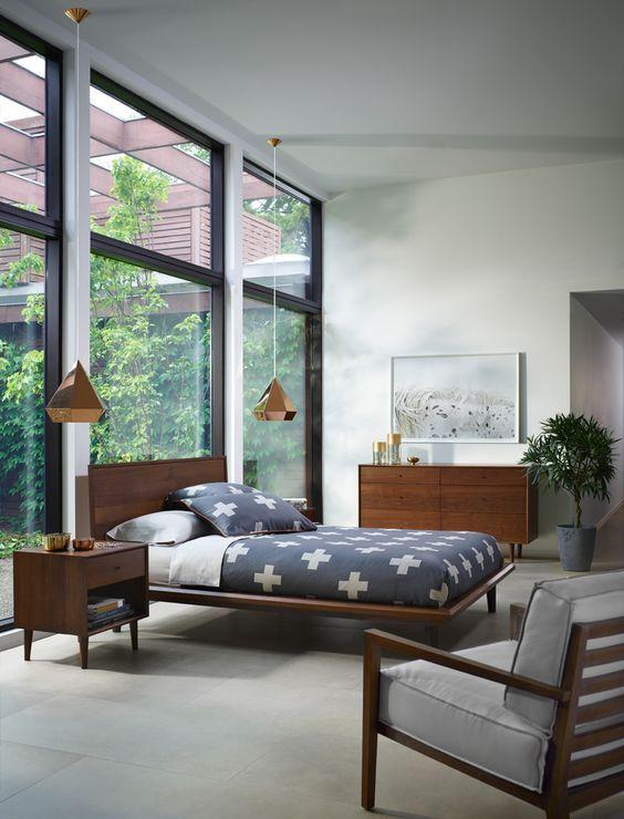 una camera da letto moderna della metà del secolo piena di luce con una parete vetrata, ricchi mobili in legno colorato, lampade a sospensione e una pianta in vaso