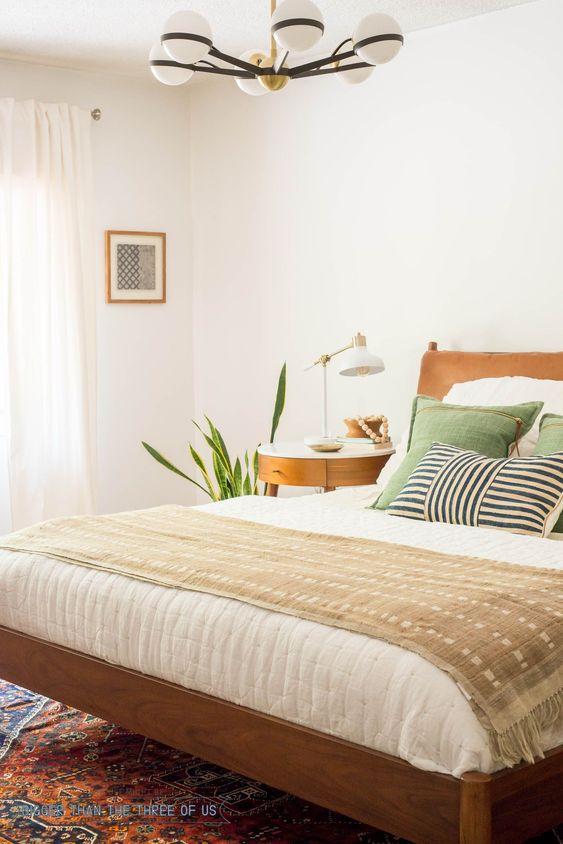 un'accogliente camera da letto moderna della metà del secolo con pareti bianche, mobili dai colori caldi, piante in vaso, un lampadario con globi e cuscini verdi
