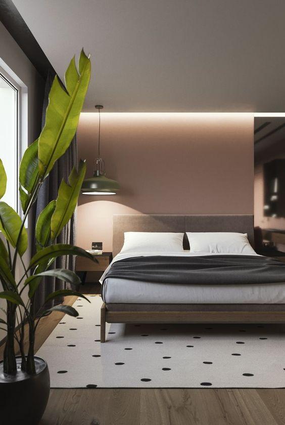 un moderno della metà del secolo incontra la camera da letto contemporanea con mobili in legno, una grande lampada a sospensione in metallo, un tappeto stampato e piante in vaso