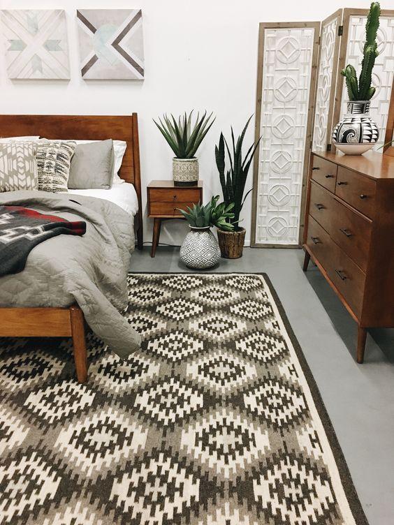 un'elegante camera da letto moderna della metà del secolo con un tappeto geometrico, mobili riccamente colorati, piante in vaso e opere d'arte