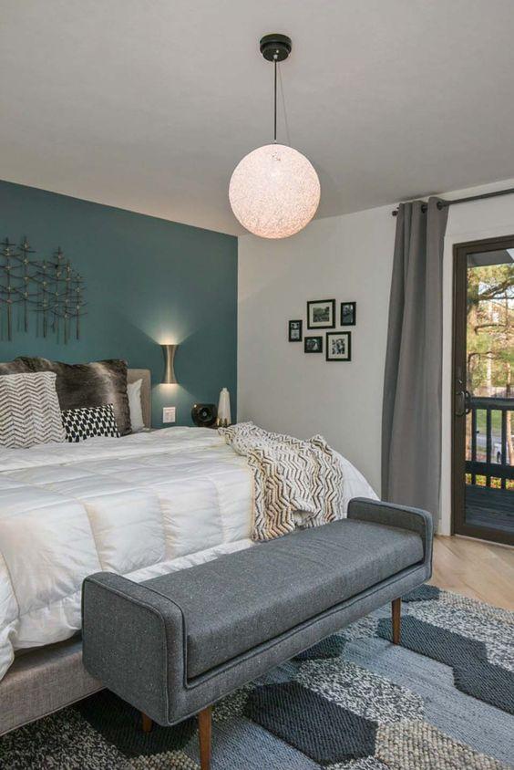 una moderna camera da letto della metà del secolo con un muro verde acqua, una panca grigia e una lampada a sospensione a globo