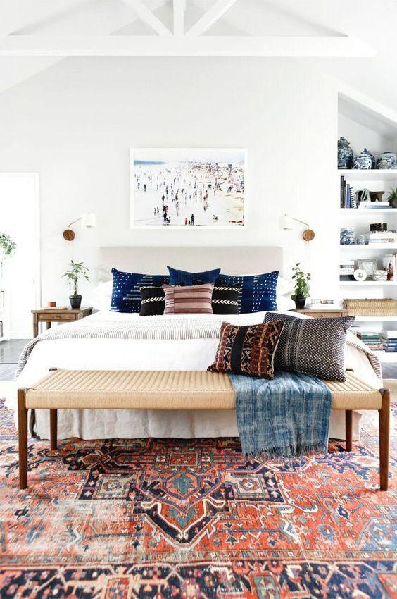 un moderno della metà del secolo incontra una camera da letto boho con un tappeto boho, una panca intrecciata, uno scaffale integrato e un'opera d'arte