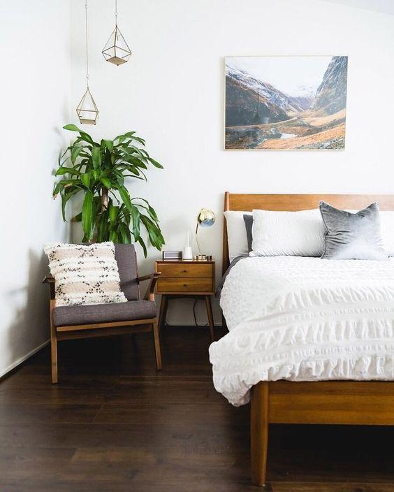 un moderno della metà del secolo incontra una camera da letto boho con mobili in legno dai colori caldi, un'opera d'arte, lampade a sospensione e una pianta in vaso