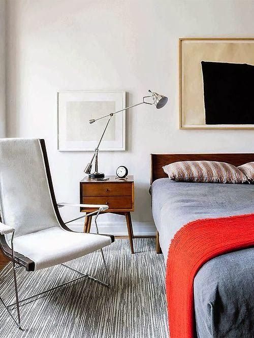 una laconica camera da letto moderna della metà del secolo con una sedia sottile accattivante, un letto accogliente, un comodino della metà del secolo e una lampada
