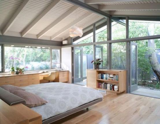 un'accogliente camera da letto moderna della metà del secolo realizzata in colori neutri, con pareti vetrate e uno spazio di lavoro con una grande scrivania