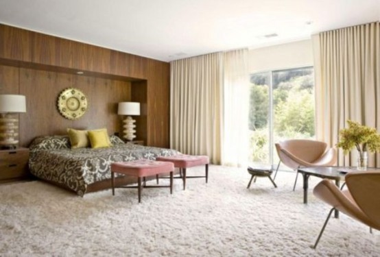 una moderna camera da letto della metà del secolo con un soffice tappeto, un muro di facciata rivestito in legno, sedie in pelle e sgabelli rosa