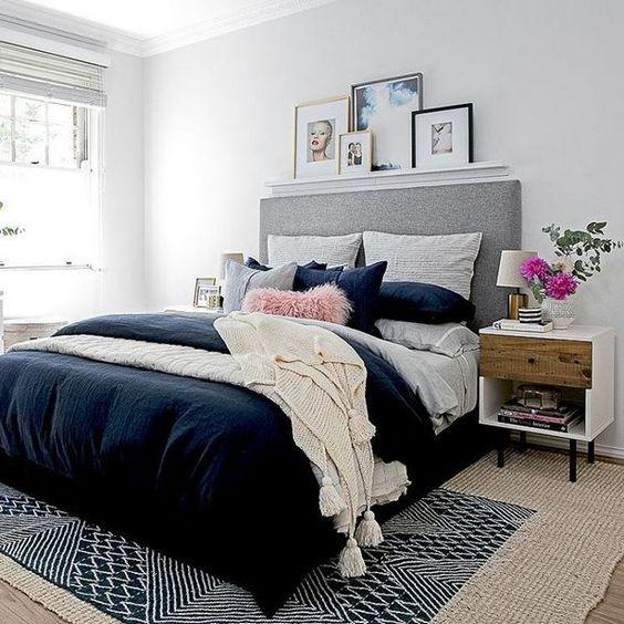 un accogliente moderno della metà del secolo incontra la camera da letto contemporanea con un tappeto stampato, un letto imbottito grigio, comodini accattivanti e opere d'arte