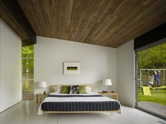 una camera da letto moderna della metà del secolo molto spaziosa e ariosa con un letto con gambe a forcina, semplici sgabelli come comodini e finestre per riempire lo spazio di luce