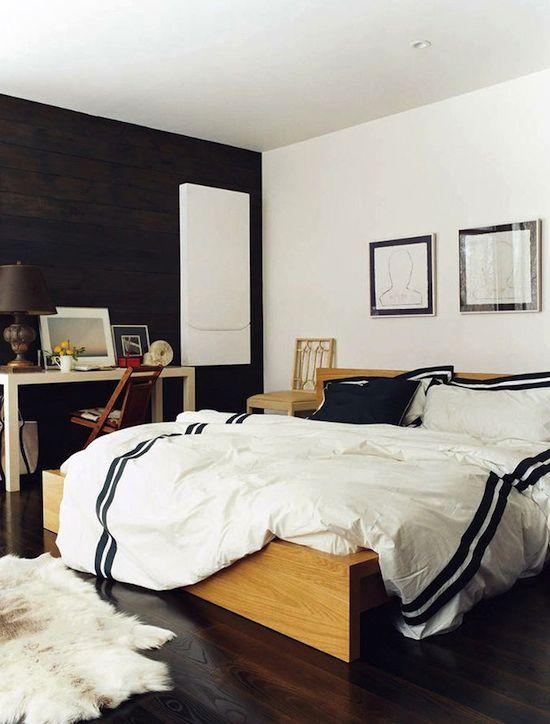 una camera da letto moderna monocromatica della metà del secolo con un letto e una console in legno più un muro nero