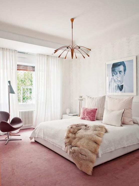 una luminosa camera da letto moderna della metà del secolo con un tappeto e una sedia rosa, un lampadario in rame, un grande letto e un'opera d'arte
