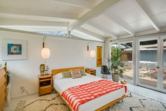 una camera da letto moderna e luminosa della metà del secolo con un letto dai colori caldi e comodini, tappeti, opere d'arte e finestre per più luce