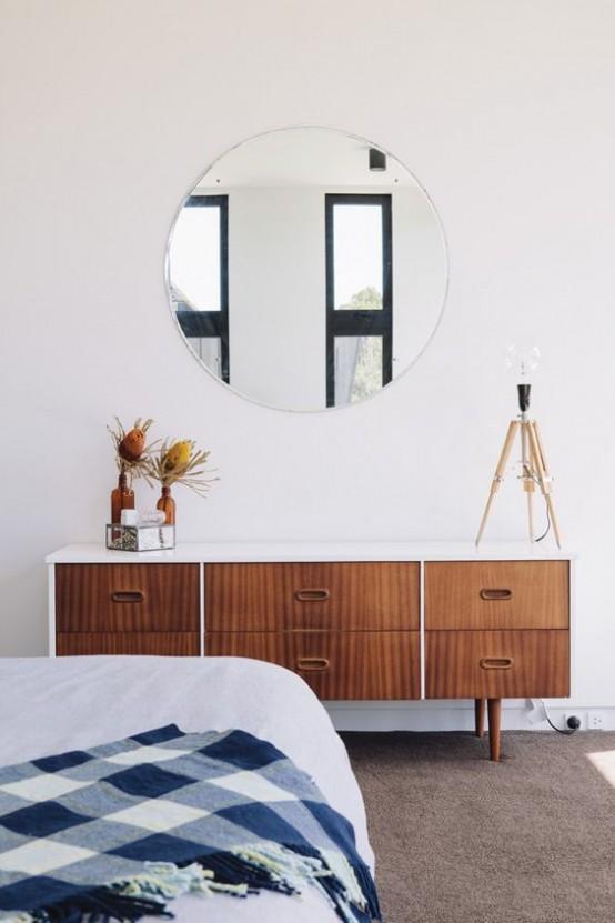 un'elegante camera da letto moderna della metà del secolo con un comò in legno, uno specchio rotondo, un grande letto e un tappeto