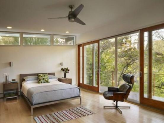 una moderna camera da letto della metà del secolo con una parete completamente vetrata, alcune piccole finestre, un letto e una grande e comoda sedia in pelle