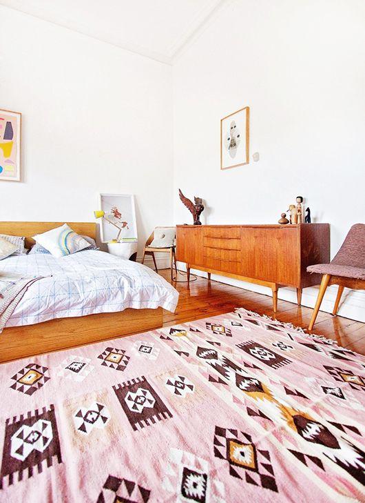 uno spazio moderno accogliente e luminoso della metà del secolo con mobili in legno dalle tonalità calde, un tappeto rosa e alcune opere d'arte
