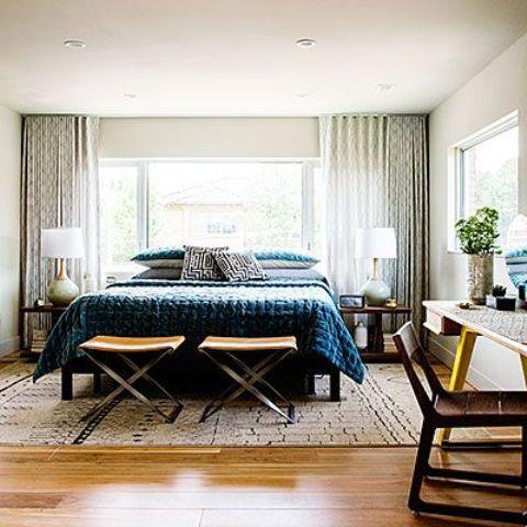 un'elegante camera da letto moderna della metà del secolo con un grande letto, comodini, scrivanie e sedie e molta luce