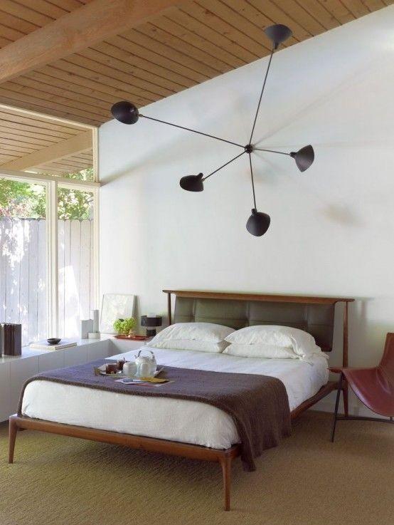 una camera da letto moderna neutra della metà del secolo con una parete vetrata, un lampadario nero, un letto con una testiera scura e alcuni mobili più chic