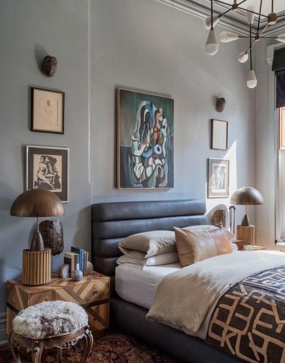 una camera da letto chic ed eclettica con un letto in pelle, opere d'arte abbinate, un lampadario chic, lampade in legno e comodini geometrici più uno sgabello in pelliccia