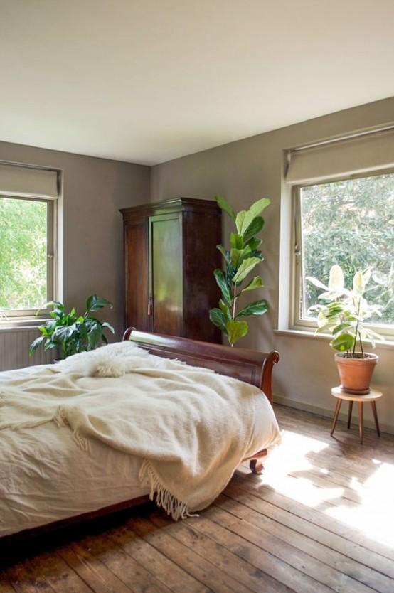 un moderno della metà del secolo incontra una camera da letto boho con ricchi mobili colorati, piante in vaso e sfumature