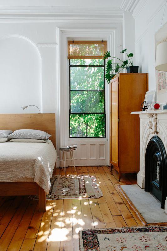 un moderno della metà del secolo incontra una camera da letto rustica con mobili in legno di colore chiaro, tappeti boho e un caminetto