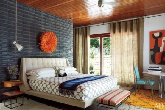 una colorata camera da letto moderna della metà del secolo con un muro di metallo grigio, un letto neutro, uno sgabello a righe e una sedia in pelle turchese
