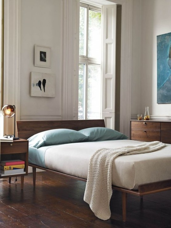 una camera da letto moderna della metà del secolo con eleganti mobili in legno colorato, opere d'arte e alcuni accenti aqua