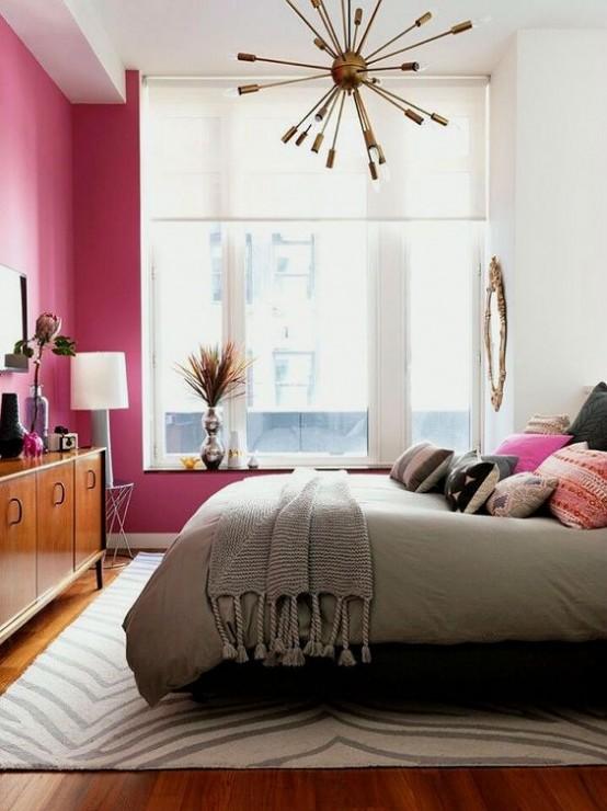 una luminosa e accogliente camera da letto moderna della metà del secolo con un muro fucsia, un ricco comò macchiato e un lampadario scoppiato in ottone