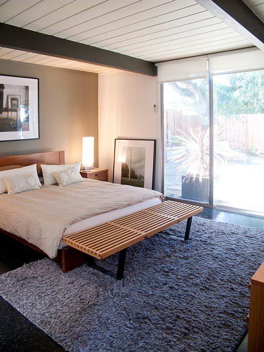 una camera da letto in bianco e nero con un muro grigio, un letto in legno, una panca in legno, un soffice tappeto grigio e una parete vetrata