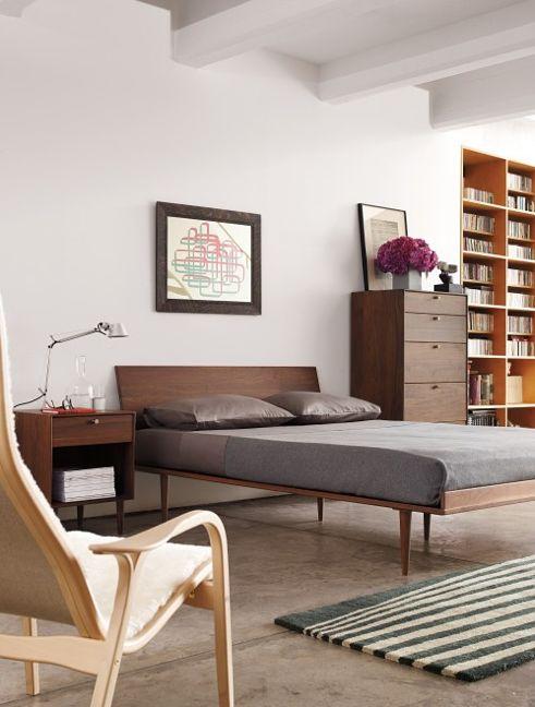 una camera da letto moderna della metà del secolo con mobili riccamente colorati, tappeti a righe e opere d'arte sembra molto fresca e piena di luce