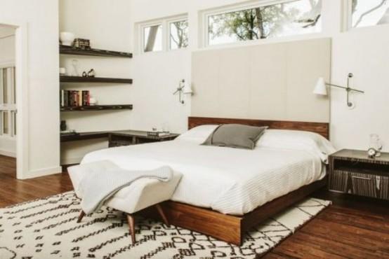 una camera da letto moderna neutra della metà del secolo con mensole in legno tinto, un ricco letto colorato con una testiera neutra e lampade da parete