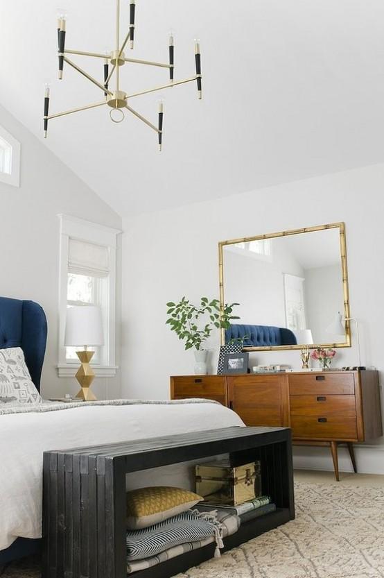 un'elegante e luminosa camera da letto moderna della metà del secolo con pareti bianche, ricchi mobili colorati, una panca nera e un lampadario dorato